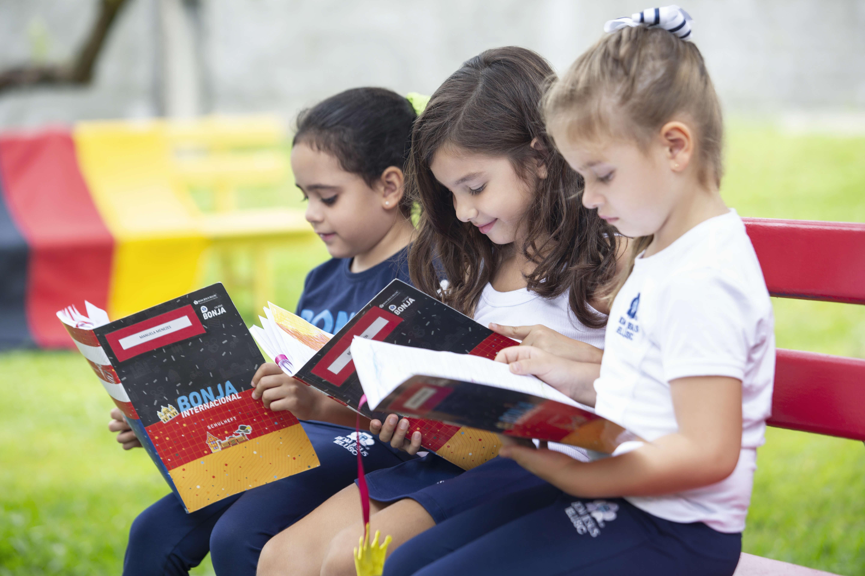 crianças lendo livros no banco do pátio